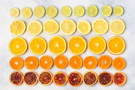 Citrus fruits rich in vitamin C, oranges, lemons, limes, satsumas arranged in the rows. Colorful background, top view Stock Photo
