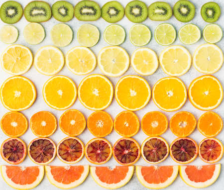 Sliced fruits rich in vitamin C, oranges, lemons, limes, satsumas, kiwis, grapefruits arranged in the rows. Colorful background, top view Stock Photo