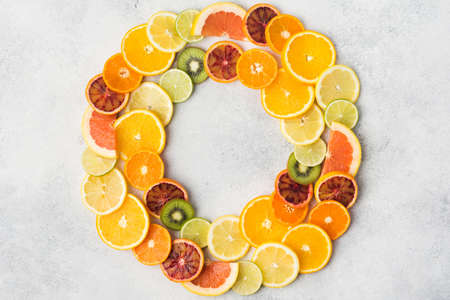 Different varieties of citrus fruits and kiwis arranged in a circle frame on white table, top view, copy space, selective focus