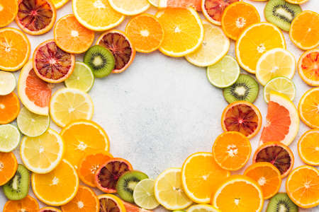 Frame made of different varieties of citrus fruits and kiwis on white table, top view, copy space, selective focus Stock Photo