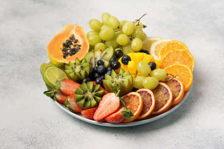 Healthy fruits and berries in rainbow colours on a white plate, strawberries, mango, grapes, bananas, grapefruit on the light grey table, copy space for text, selective focus