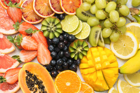 Healthy colourful fruits in rainbow colours, strawberries, mango, grapes, bananas, grapefruit on the off white table, top view, selective focus Stock Photo