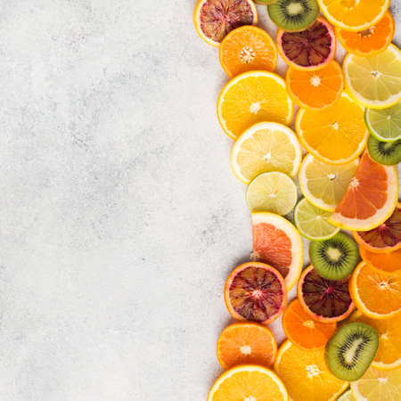 Assortment of citrus fruits and kiwis on off white table background, top view, copy space, square selective focus Stock Photo