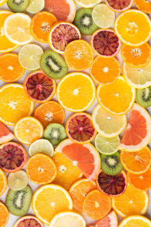 Colourful fruit pattern, oranges, clementines, blood oranges, kiwis and grapefruits on white table background, top view, selective focus
