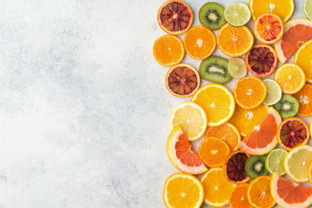 Assortment of citrus fruits and kiwis on white table background, top view, copy space, selective focus