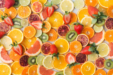 Colourful fruit pattern, oranges, clementines, blood oranges, kiwis, strawberries and grapefruits on white table background, top view, selective focus