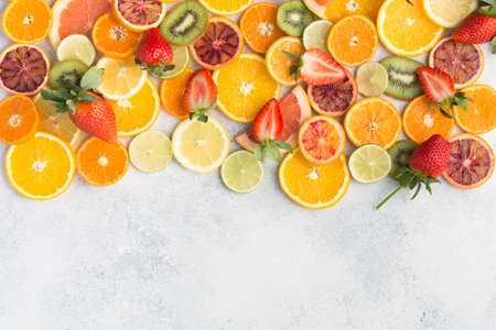 Colourful fruits background, oranges, clementines, blood oranges, kiwis, strawberries and grapefruits on white table background, top view, copy space for text, selective focus