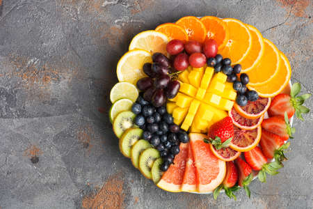 Assortment of cut fruits in rainbow colors oranges grapes mango strawberries kiwis blueberries grapefruit on the grey concrete table, top view, copy space, selective focus