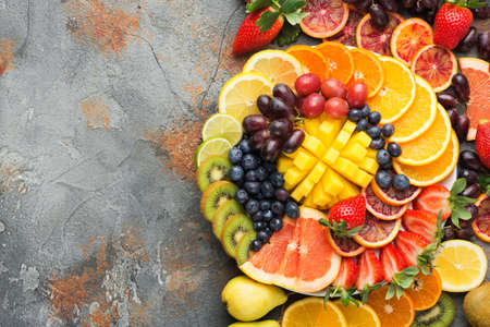 Colorful cut fruits in rainbow colors oranges grapes mango strawberries kiwis blueberries grapefruit on the grey concrete table, top view, copy space, selective focus