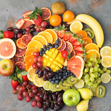 Colorful cut fruits platter in rainbow colors oranges grapes mango strawberries kiwis blueberries grapefruit on the grey concrete table arranged in circle, top view, selective focus Stock Photo