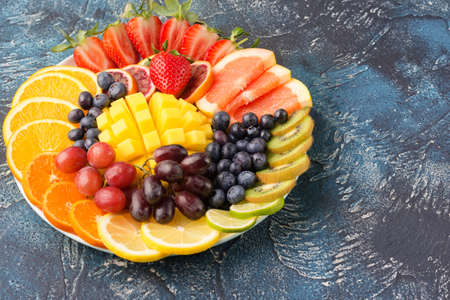 Healthy fruits and berries platter in rainbow colors close up, strawberries, mango, grapes, oranges, kiwis, lemons on the blue table, copy space for text, selective focus on mango
