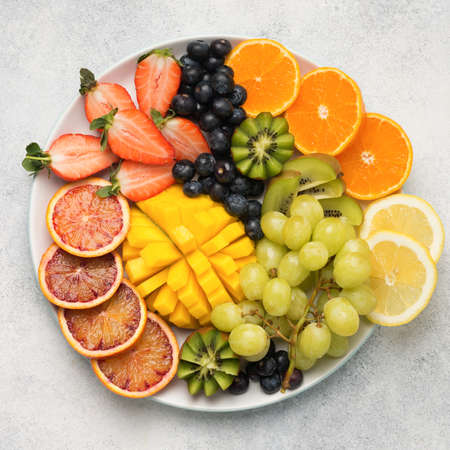 Colourful fruits and berries in rainbow colours, on a plate, strawberries, mango, grapes, bananas, grapefruit on the off white table, square, copy space for text, selective focus Stock Photo