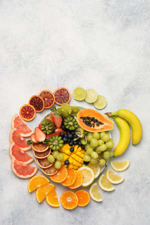 Top view of healthy fruits in rainbow colours, arranged in a circle, strawberries, mango, grapes, bananas, grapefruit on the off white table, vertical, copy space for text, selective focus