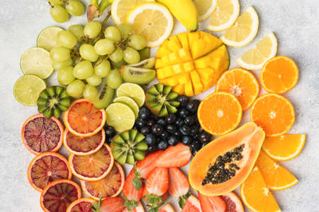 Top view of healthy fruits in rainbow colours, strawberries, mango, grapes, bananas, grapefruit on the off white table, copy space for text, selective focus Stock Photo
