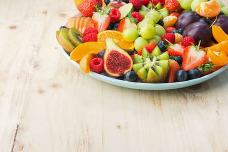 Healthy fruit and berries platter, strawberries raspberries oranges plums apples kiwis grapes blueberries on the light wooden pine table, close up, copy space for text, square, selective focus