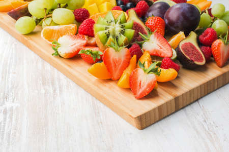Healthy raw fruits and berries platter, strawberries raspberries oranges plums apples kiwis grapes blueberries, mango on the serving board, top view, copy space, selective focus