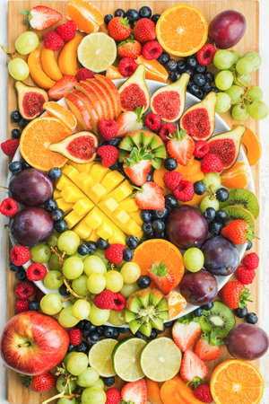 Healthy raw fruits and berries platter background, strawberries raspberries oranges plums apples kiwis grapes blueberries, mango on the serving board, top view, vertcial, selective focus