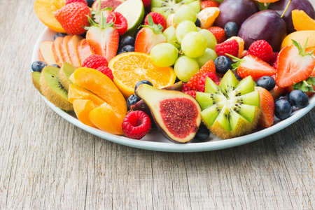 Healthy fruit and berries platter, strawberries raspberries oranges plums apples kiwis grapes blueberries on the dark grey wooden table, close up, copy space for text, selective focus