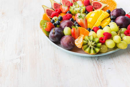 Healthy raw fruits and berries plate, strawberries raspberries oranges plums apples kiwis grapes blueberries, mango on the white woorden table, selective focus
