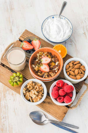 Oat free paleo nut and fruit granola served with fruits and berries, nut milk, coconut yogurt, vertical, selective focus