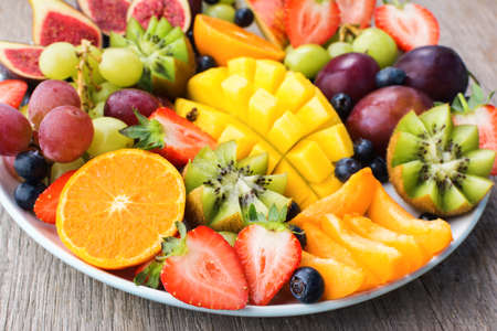 Assorted fruits and berries platter, strawberries blueberries, mango orange, apple, grapes, kiwis on the grey wood background, selective focus