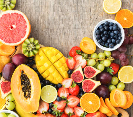 Top view of rainbow colored fruits, strawberries blueberries, mango orange, grapefruit, banana papaya apple, grapes, kiwis on the grey wood background, copy space for text, square, selective focus