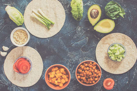 Ingredients for vegan tortillas: chickpeas, butternut squash, spring onion, cucumber, avocado on the dark blue table, top view