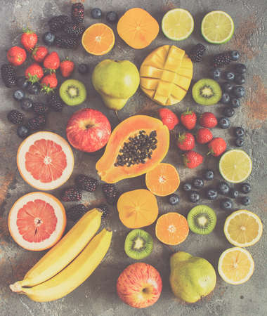 Different rainbow colored fruits, strawberries, blueberries, mango, orange, grapefruit, banana, apple, grapes, kiwis on the grey background, above view, toned, selective focus