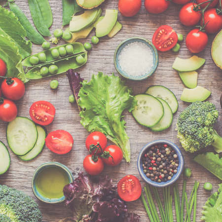 Cut vegetables for salad, fresh tomatoes, cucumber, avocado, lettuce, spring onion, broccoli on the grey wooden table, square, toned, selective focus Stock Photo