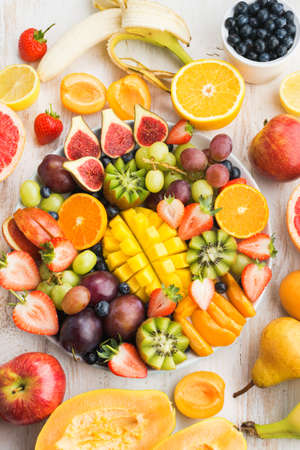 Variety of cut fruits and berries platter, strawberries blueberries, mango orange, apple, grapes, kiwis on the white wood background, copy space for text, layout, top view, selective focus Stock Photo