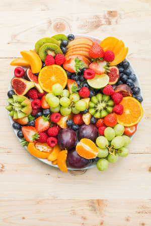 Healthy fruit platter, strawberries raspberries oranges plums apples kiwis grapes blueberries on the light wooden pine table, top view, copy space for text, selective focus