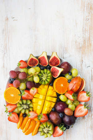 Variety of cut fruits and berries platter, strawberries blueberries, mango orange, apple, grapes, kiwis on the white wood background, copy space for text, vertical, top view, selective focus Stock Photo