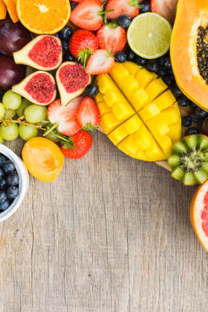 Top view of assorted fruits, strawberries blueberries, mango orange, grapefruit, banana papaya apple, grapes, kiwis on the grey wood background, copy space for text, vertical, selective focus
