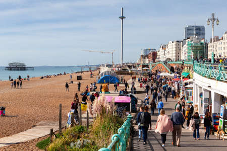 Brighton, England, October 07, 2018. People on on busy shingle beach in Brighton, the British Airways i360 and ruined West pier on the background, selective focus