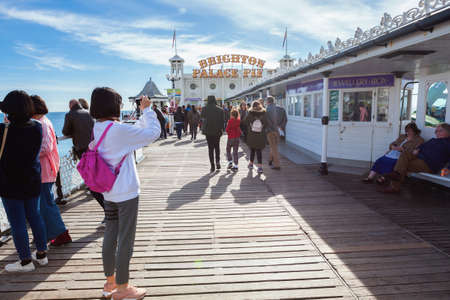 Brighton, England, October 07, 2018. People on Brighton pier, taking photographs and walking, East Sussex, UK, selective focus Editorial