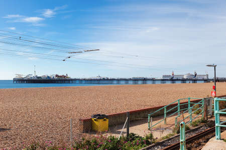 Brighton, England, October 07, 2018. People on the zipwire on the beach with Brighton pier, sea and shingle beach on the background, selective focus Editorial