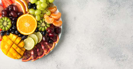 Raw fruits berries assortment platter on the white plate, on the off white table, top view, copy space Stock Photo