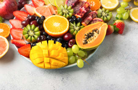 Assortment of raw fruits berries, mango, oranges, kiwi strawberries, blueberries grapefruit grapes, bananas apples on the white plate, on the off white table, copy space Stock Photo - 109426642