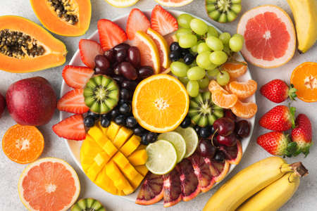Raw fruits berries platter, mango, oranges, kiwi strawberries, blueberries grapefruit grapes, bananas apples on the white plate, on the off white table, top view, selective focus Stock Photo