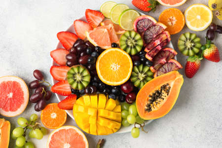 Raw fruits berries platter, mango, oranges, kiwi strawberries, blueberries grapefruit grapes on the white plate, on the off white table, top view, copy space