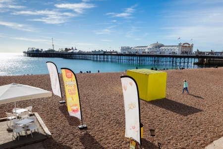 Brighton, England, October 07, 2018. People on on the beach with Brighton pier on the background, sea and shingle beach selective focus Editorial