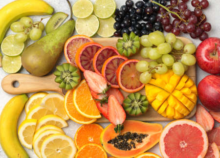 Healthy colourful fruits in rainbow colours, strawberries, mango, grapes, bananas, grapefruit on the off white table, side view, selective focus Stock Photo - 109433542