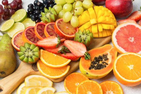 Healthy colourful fruits in rainbow colours, strawberries, mango, grapes, bananas, grapefruit on the off white table, side view, selective focus