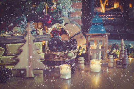 Beautiful Christmas setting, decorated lit up Christmas tree with baubles and ornaments, fireplace with woodburner, lantern, stars and garlands, created snow, toned, selective focus