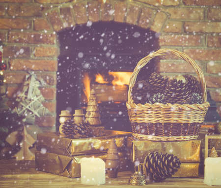 Christmas composition, pine cones in wicker basket, wooden ornaments, golden presents on the table in front of fireplace with woodburner, candles and garlands, selective focus, snow, toned