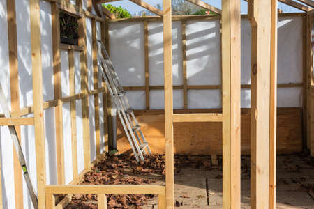 Building summer house or shed in the garden, wooden structure, waterproofed, on a stone base, selective focus Stock Photo