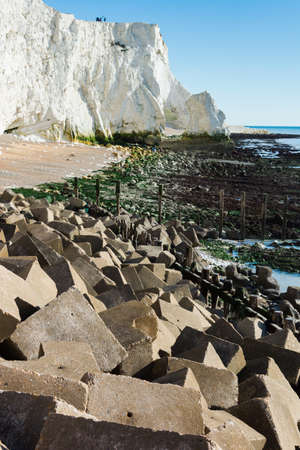 View of Seaford head from the splash point, cliffs, sea and blue sky, concrete blocks used as sea defense in the front, East Sussex. England, near Seven Sisters National park, selective focus