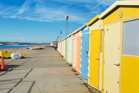 Seaside beach huts on Seaford beach, East Sussex. England, view of pebbly beach and blue sea, Newhaven town on the background, selective focus Stock Photo