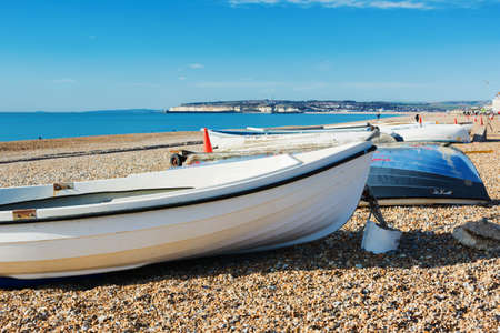 Fishing boats in Seaford beach, East Sussex. England, pebbly beach and blue sea, view of Newhaven town, selective focus
