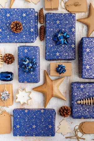 Creative christmas arrangement. Presents in dark blue wrapping paper with silver stars and sparkles, wooden decorations, ornaments, paper tags on white table, top view, selective focus